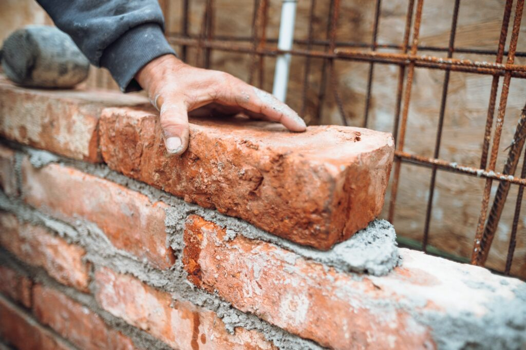 worker laying bricks and building walls on construction site. Detail of hand adjusting